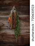 Small photo of abnormal shaped carrot hanging on a wooden wall