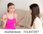 Small photo of Frustrated young girl sitting on sofa at home, tells girlfriend about personal problems. Best friends chat about private matters. Sister carefully listens to her siblings rant without interrupting.