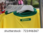 Small photo of yellow and green t-shirts with the text BRASIL which means Brazil for sale in the specialized sports shop
