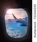 Stock photo the wing of airplane and sunset on sky blue or azure sky and beautiful cloud when look out the 722162233