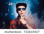 a hipster in a cap sits on a... | Shutterstock . vector #722614327