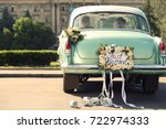 Small photo of Wedding couple in car decorated with plate JUST MARRIED and cans outdoors