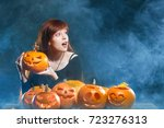 Small photo of Surprised red haired woman with Halloween pumpkins over smoky background looking with amazement to side at blank copy space