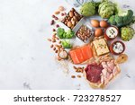 Small photo of Assortment of healthy protein source and body building food. Meat beef salmon chicken breast eggs dairy products cheese yogurt beans artichokes broccoli nuts oat meal. Copy space background, top view