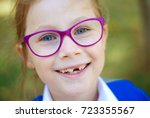 Small photo of A 7-year-old Years old school girl smiling. Portret. Green blured background.