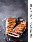 Small photo of Grilled chicken fillets on slate plate. Gray concrete background. top view. copy space