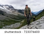 Small photo of Outdoorsy adventurous man is hiking up a rock face to the top of the mountain