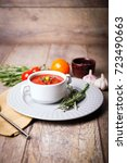 Small photo of Red ukrainian borsch with two garlic, parsley and other different vegetables in a plate on a wooden table. Close-up of dish. Copy space. Food concept.