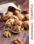 Small photo of Walnut kernels and whole walnuts on rustic old wooden table.
