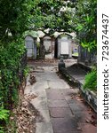 Small photo of Trees seem to swallow a walkway that leads through a spooky cemetery in New Orleans