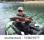 Small photo of Man fly fishing from a pontoon or float tube with his catch, large trout fish (Brook Trout hybrid with Lake Trout, called Splake)