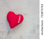Small photo of Handmade textile heart was broken and sewed again with white thread on a gray concrete background, square format