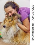 Small photo of Pretty smiling brunette woman is hugging her friend cute beautiful rough collie dog, scratching pleasantly it's ears with admiration, tenderness, love, trust