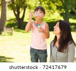 girl blowing bubbles with her... | Shutterstock . vector #72417679