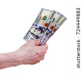 Small photo of Old hand holding three hundred dollars, isolated on a white background.
