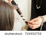 hairstylist curling hair client ... | Shutterstock . vector #724552753