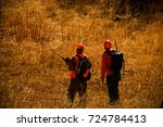 hunters stand in a field clad... | Shutterstock . vector #724784413