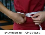Small photo of The woman measuring her waist with measure tape.
