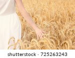 young woman touching wheat in... | Shutterstock . vector #725263243