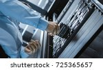 Small photo of Long Angle Shot In Fully Working Data Center IT Engineer Installs Hard Drive into Server Rack. Detailed and Technically Accurate Footage.