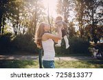 young family walking in the park   Shutterstock . vector #725813377