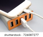 Small photo of Close-up image of smart phone charging with multiport USB power adaptor on gray background, Selective focus