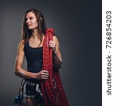 Small photo of Studio portrait of female free clamber holds, climbing rope over grey background.