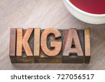 Small photo of ikigai - Japanese concept - a reason for being or a reason to wake up - word abstract in vintage wood type with a cup of tea