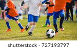 Small photo of Running Children Football Soccer Players with Ball. Footballers Kicking Football Match on the Pitch. Young Teen Soccer Game. Youth Sport Background