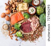 Small photo of Assortment of healthy protein source and body building food. Meat beef salmon chicken breast eggs dairy products cheese yogurt beans artichokes broccoli nuts oat meal. Top view