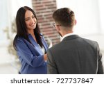Small photo of Smiling businesswoman communicating with male colleague in the o
