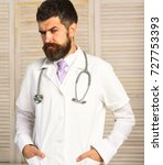 Small photo of Healthcare and treatment concept. Physician with thoughtful face ready to diagnose. Man in surgical uniform with stethoscope on neck on wooden background. Doctor with beard in white medical coat