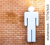 Small photo of The orange brick wall has a white male figure, should be used to describe. Background or wallpaper