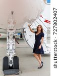 Small photo of young beautiful woman stands next to the ladder and chassis the business jet