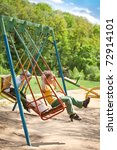 Two five year old boy swinging on a swing in the park on the playground - stock photo