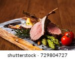 Small photo of Baked lamb loin, served with asparagus. Dark background.