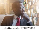 Small photo of Horizontal closeup of young handsome African American businessman pressing his chin with fist while looking dreamily to street as if waiting for realization of ambitious plans for enterprise he leads