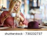 blonde woman drinking coffee in ... | Shutterstock . vector #730232737
