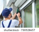 man installing roller shutter... | Shutterstock . vector #730528657