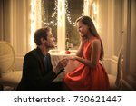 Small photo of Handsome man proposing a beautiful woman to marry him in an elegant restaurant