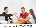 Small photo of Estate agent giving key to couple in office