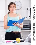 Small photo of Woman beginner is signing agreement papers of financial nature at office.