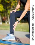 Small photo of Female runner touching cramped calf at morning jogging. Achilles tendon pain or injury concept background