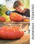 little boy carving a pumpkin... | Shutterstock . vector #731661463