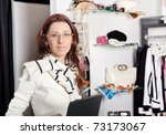 Shop assistant with laptop working in clothing store - stock photo