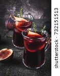 Small photo of Fall and winter red sangria cocktail with thyme and figs, on black stone table, copy space