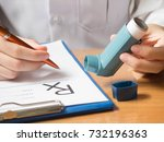 Small photo of Close up of doctor hand holding blue asthma inhaler and writing medical prescription on rx form for treatment asthma/COPD diseases on physician's desk at hospital. Healthcare concept. Selective focus.