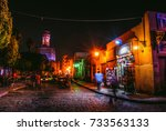 Small photo of Cairo, Egypt - 2011 ( Muizz Street at night with people and car moving with the Mosque of al-Hakim nicknamed al-Anwar is visible in the background )
