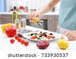 woman pouring olive oil onto... | Shutterstock . vector #733930537