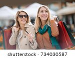happy friends shopping. two... | Shutterstock . vector #734030587